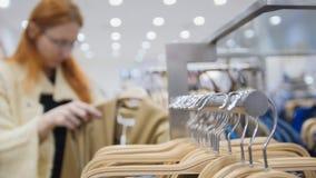 Una fila de suspensiones en una tienda de ropa del ` s de las mujeres enmascarado Foto de archivo libre de regalías