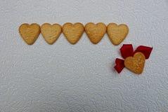 Una fila dei cuori marroni dai biscotti e di uno con i petali rosa fotografia stock