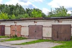 Una fila dei garage del mattone con i portoni arrugginiti del metallo La Russia Fotografia Stock