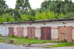 Una fila dei garage del mattone con i portoni arrugginiti del metallo La Russia Fotografie Stock