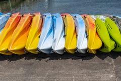 Una fila dei kajak brillantemente colorati che si siedono sulla terra, colori ha incluso verde e blu gialli fotografie stock libere da diritti