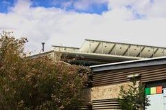 Una fila dei pannelli solari su un tetto australiano della scuola alzato per prendere il sole Immagine Stock Libera da Diritti