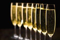 Una fila dei vetri del champagne su un fondo nero Foc selettivo Fotografie Stock Libere da Diritti