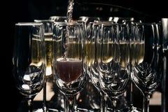Una fila dei vetri riempiti di champagne è pronto allineato ad essere servito Immagini Stock Libere da Diritti