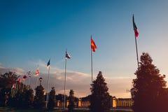 Una fila delle bandiere di volo delle nazioni sul fondo del cielo di tramonto Bandiere dei paesi differenti nel parco di estate Fotografia Stock