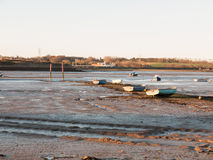 Una fila delle barche ha parcheggiato nel fango con la marea fuori Immagini Stock Libere da Diritti