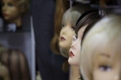 Una fila delle donne dei manichini su uno scaffale in un negozio della parrucca immagine stock
