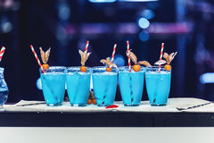Una fila di cinque cocktail blu con ghiaccio ed i tubi, luci posteriori Fotografie Stock Libere da Diritti