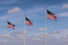 Una fila di tre bandiere americane con il cielo nuvoloso fotografia stock