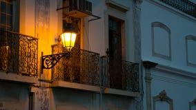 Una fila di vecchie case con i balconi alla notte in Algarve Portogallo del sud si è accesa soltanto da una lampada di via gialla immagini stock libere da diritti
