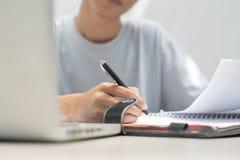 Una fine su con la mano che fa lavoro domestico con la penna ed il computer portatile immagine stock