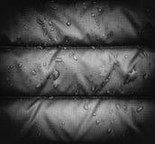 Una fine su del tessuto impermeabile blu con le goccioline di acqua, effetto del rivestimento della pioggia di vignettatura fotografie stock