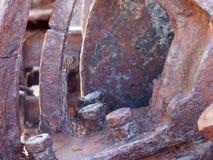 una fine su delle bielle e degli ingranaggi arrugginiti del ferro con i bulloni su vecchio macchinario corroso immagine stock