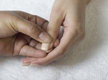 Una fine su delle mani femminili che fanno manicure Fotografie Stock