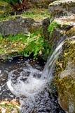 Una fine su di bello waterful, l'acqua crea un effetto di ondulazione mentre spruzza nello stagno qui sotto immagini stock