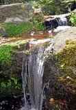 Una fine su di chiara acqua che cade da un livello dello stagno del giardino a quella seguente qui sotto fotografie stock