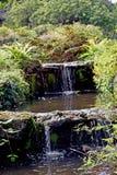 Una fine su di chiara acqua che cade da un livello dello stagno del giardino a quella seguente qui sotto fotografia stock