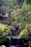Una fine su di chiara acqua che cade da un livello dello stagno del giardino a quella seguente qui sotto immagini stock libere da diritti