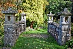 Una fine su di questo ponte di pietra romantico con il ` s dell'albero e degli arbusti di tutte le dimensioni e forme differenti  fotografia stock libera da diritti