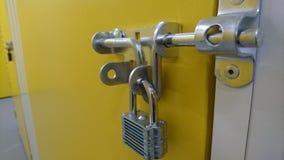 Una fine su di un lucchetto e di un paletto di alluminio su una porta dell'unità di stoccaggio Immagine Stock Libera da Diritti