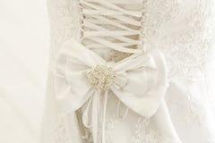 Una fine su di un vestito da sposa con un grande arco di seta Fotografia Stock Libera da Diritti