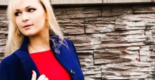 Una fine su di una donna che fa una pausa un muro di mattoni Immagine Stock