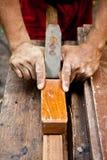 Carpentiere che lavora ad un pezzo di legno. Immagini Stock