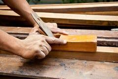 Carpentiere che lavora ad un pezzo di legno. Fotografia Stock