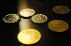 Una fine sullo sguardo delle monete dello spargimento fotografie stock