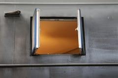 Una finestra aperta in una parete d'acciaio con bagliore arancione dentro immagini stock