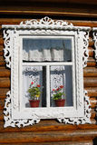 Una finestra di una casa di legno della contea decorata dalle strutture bianche Immagine Stock Libera da Diritti