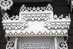 Una finestra di una casa di legno della contea decorata dalle strutture bianche Immagini Stock