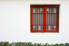 Una finestra rossa contro il fondo bianco della parete fotografia stock libera da diritti