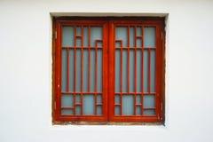 Una finestra rossa contro il fondo bianco della parete immagine stock