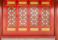 Una finestra rossa di scolpisce i modelli o le progettazioni sulla lavorazione del legno Immagine Stock Libera da Diritti