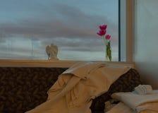 Una finestra in una stanza di ospedale con le nuvole di sera fuori ed i fiori in un barattolo, in una statua di angelo alcune cop immagini stock