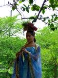 Una flauta de bambú blowning vestida de la mujer Foto de archivo libre de regalías