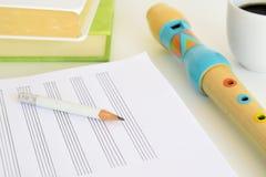 Una flauta, un lápiz y una hoja de música al lado de algunos libros y de una taza de café en un escritorio en una sala de clase e Foto de archivo