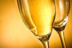 Una flauto di champagne e di uno vuoti con le bolle e lo spazio dorati per testo Immagine Stock