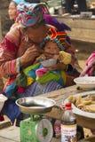 Una flor Hmong que alimenta a su bebé en Bac Ha Foto de archivo
