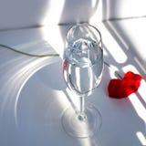 Una flor roja de la amapola en la tabla blanca con la luz y las sombras del sol del contraste y la copa de vino con la opinión su fotografía de archivo