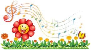 Una flor roja en el jardín con las notas musicales Fotos de archivo libres de regalías