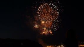 Una folla della gente guarda i fuochi d'artificio variopinti e celebra stock footage