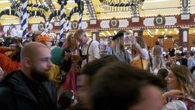 Una folla della gente ubriaca in costumi nazionali beve la birra e si diverte dentro un corridoio di birra enorme La Baviera, Ger archivi video