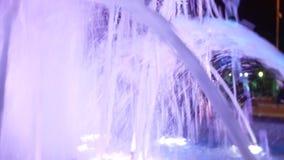 Una fontana con illuminazione colorata dell'acqua, nella sera primo piano, sfuocatura, 4k archivi video