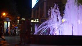 Una fontana con illuminazione colorata dell'acqua, nella sera primo piano, sfuocatura, 4k video d archivio