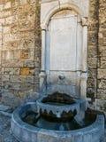 Una fontanella medievale antica Fotografie Stock