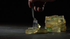 Una forcella pizzica lentamente un pezzo di gelatina stock footage