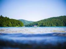 Una foresta su un lago con una barca nel fratempo immagine stock