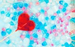 Una forma del cuore della caramella contro lo sfondo di trasparente, di bianco, il rosa ed i cubetti di ghiaccio blu Modello fres fotografie stock
